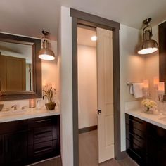 The luxurious, spa-style master bathroom from the HGTV Dream Home 2014 features two separate vanities with espresso-finished Shaker style cabinets and sleek white countertops mixed with hand-scraped bamboo floors and brushed nickel photographer's pendants. A sliding door adds privacy to the commode.