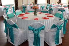 White polyester tablecloths and chair covers, coral polyester napkins, and pool blue satin sashes. | AM Linen Rental