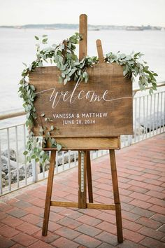 welcome board on easel with flower garland. Subtle, beautiful, lovely. #LauraPearceLTD