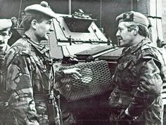Lieutenant Colonel Garry Barnett, left, commanded the 1st Battalion The Black Watch in Northern Ireland in 1980. He is speaking to Brigadier Riddell.  The soldiers wear camouflage jackets. Lieutenant Colonel Barnett wears a fawn Tam O'Shanter bonnet with a red hackle, seen clearly in the bonnet of the soldier behind. Brigadier Riddell wears a fawn Tam O'Shanter bonnet with a Leslie tartan patch and a General Officer's badge of a crown and lion. Brigadier Riddell was a Royal Highland…
