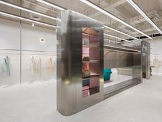 A stainless steel partition with rose-tinted windows sits at the centre of this womenswear store in Hangzhou, China, designed by Xian Xiang Design. Retail Store Design, Retail Shop, Cottage Interiors, Shop Interiors, Shop Facade, Futuristic Interior, Terrazzo Flooring, Loft, Retail Interior