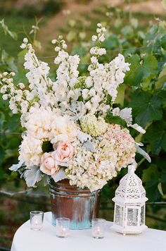 The ceremony guestbook table will feature a vintage planter filled with cream hydrangeas, ivory stock flowers, green bells of Ireland, white tulips, blush pink spray roses, blue forget-me-nots, Queen Anne's lace, seeded eucalyptus, seasonal greenry, and grey dusty miller.