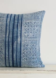 This unique cushion cover was made by piecing together two panels of a vintage Hmong textile. The front is indigo blue with an intricate