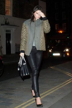 Kendall Jenner wears a quilted olive green jacket, leather pants, pointed-toe heels, and a Saint Laurent satchel