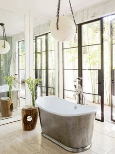 Bathroom with travertine floors, mirrored walls, and alabaster chandelier