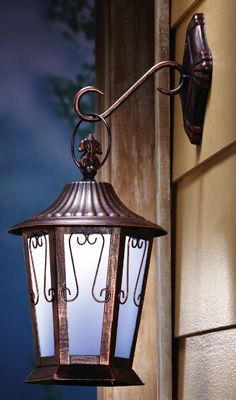 "Traditional coach style lantern lights up your home's exterior. Its built-in solar collector powers the LED glow that automatically switches on each night at twilight. Includes 1 AA rechargeable battery. Bronze finish metal and glass. 9 3/4""L x 7""W x 17""H."