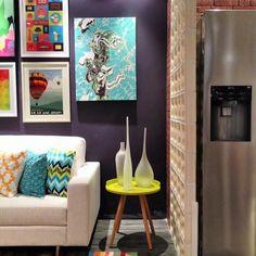 """À pedidos, vou sempre incluir aqui Inspirações """"low cost"""". Nesse projeto, a separação do living com a cozinha foi feita com uma divisória de cobogos. A parede principal da sala foi pintada com uma cor de destaque. Uma dica legal para os quadros é você selecionar imagens que te agradam, imprimir e mandar emoldurar. Fica lindo e o custo, vale muito à pena."""