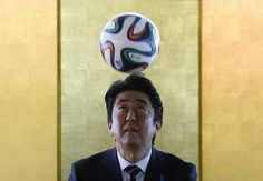 Japan's Prime Minister Shinzo Abe heads the ball during a meeting with Brazilian soccer players in Brasilia, August 1, 2014. REUTERS/Ueslei Marcelino
