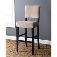 This sturdy bar stool features a birch wood construction covered with velvet fabric upholstery for a smooth feel. The brass nailhead trim frames the back of the chair so it can lend style to your spac