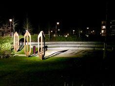 Weverslabyrint met 3 cortenstaal spoelen en symboolstenen Atelier Vandré Helmond by night.