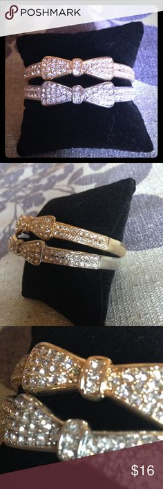 HP Set of Silver and Gold Crystal Bow Bangles Host Pick: 7/13- Classic Chic Party Selling as a set of two- silver tone and gold tone bow bangles.  Slip on style with crystal bows on the front and along the sides of the bangle.  Stones stop mid-way around and a smooth finish completes the bangle around the back.  Please note: one stone is missing from the gold bangle (indicated in third pic) but not noticeable when wearing (see modeling in fourth pic).  New and never worn. Jewelry Bracelets