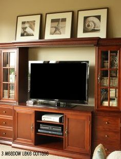 photos over tv cabinet - this may be an option but would want open vs glass encased side shelves