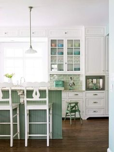 Taking+its+cue+from+the+ocean,+the+sea+green+shade+in+this+kitchen+creates+a+light+and+airy+atmosphere.+If+you+love+a+particular+color+but+think+it+might+be+too+intense+to+use+in+your+decor,+opt+for+a+neutral-hinted+version.+While+sea+greens+are+often+more+vibrant,+the+shade+used+on+the+island+is+toned+down+with+a+bit+of+gray.+The+same+shade+is+variegated+with+clouds+of+white+on+the+backsplash+tile+for+an+effervescent+look.