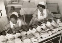 Nurses showing the eleven babies that were born on New Year's Day 1933 in a hospital in Berlin, Germany.