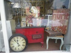 I love this window display with a Vintage chest of drawers painted in Annie Sloan Empire Red.   Kelly Rae wall art  mixed with  retro accessories