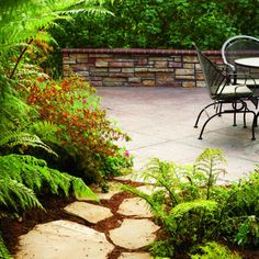 Decorative and functional, a dry-laid flagstone and mulch path leads the way to a patio retreat.    A border of ferns and red-flowered Cuphea ignea creates a leafy entry.  Stone can be warm and magical!  In the back planter, a tall mallow hedge screens a vegetable garden.