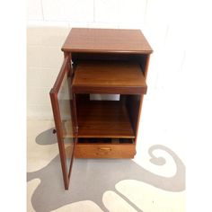 Lovely Mid Century Modern Stereo Cabinet In Teak With Glass Door And One Drawer  With Small Wheels Dimensions: W 22 D 20 H Used: An Item That Has Been