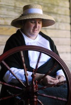 Meet artisans such as this spinner spinning wool carding into yarn at Cracker Country.