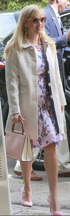 Who made  Reese Witherspoon's pink sunglasses, white coat, pumps, floral dress, handbag, and white coat?