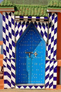 The Roof Garden of a Hotel in Sidi Ifni, Morocco: really cool door but I especially like the triangle tiles that they used to create a harlequin design