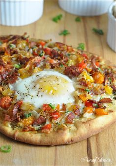 Pizza for breakfast.  2 naan flatbreads • 1 tablespoon pesto, divided • 4 strips bacon, cut into 1/2-inch pieces • 1/2 cup diced red or orange bell pepper • 1/2 cup diced sweet onion • 1/2 tablespoon unsalted butter • 1 cup Simply Potatoes shredded hash browns (found in the refrigerator section at the market) • 1 1/2 cups Italian blend shredded cheese • 1 scallion, diced • 2 eggs • salt and pepper