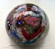 Paperweights generally are of solid glass, and have a flat base and a domed top, which acts like a lens to magnify and make the parts within move as it is handled. Glass Marbles, Glass Paperweights, Glass Ball, Paper Weights, Hand Blown Glass, Rainbow Colors, All The Colors, Jimmy Smith, Art Pieces