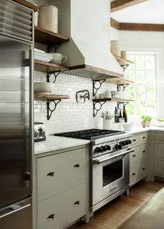 Open rustic shelving with iron supports  Contrasts with creamy subway tile Grayed green cabinets ties it all together
