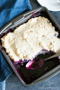 A pan of gluten free blueberry cobbler with two portions missing.