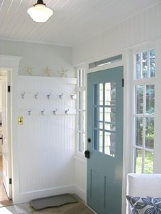 Love the aqua door! :) This century home's back entry/ mudroom, laundry room and potting room is just off the kitchen and is updated with a soft dove grey contrasted by the pop of seaside inspired blue on the farmhouse back door.(Boca Raton by Benjamin Moore). The windows which were once a deep cream are original to the porch and updated to a fresh crisp Oxford White by Benjamin Moore.