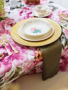 Gold charger by A Chair Affair Rentals with floral china and tablecloth.