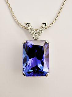 Emerald cut tanzanite pendant set in platinum with a diamond set 'V' shaped platinum shackle.