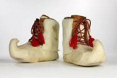 This is a pair of boots from the Saami peopleof Finland.  Made of white reindeer hide, the curled up toes are a signature detail for Saami footwear.  This pair was made in Finland by Helena Naakkaalaajaarvi. White reindeer is considered rare. Boots like these, while cozy would also be worn for important ceremonies and weddings