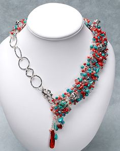 Fine-gauge silver wire is interwoven with layers of turquoise nuggets and beads, pieces of coral, pearls, crystals, and silver accent beads to create a collar-style necklace. I made the large rings and clasp from PMC. The asymmetrical design is secured with a front-loop clasp embedded in the beadwork.
