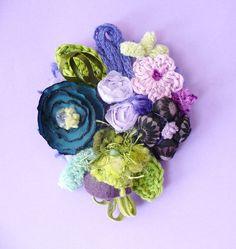 Spille con fiori in tessuto stampato fantasia e non, con fiorellini a crochet, passamanerie e filati.