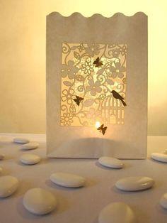 Diese wunderschöne weiße Lichtertüte mit filligranem Blüten- und Vogelkäfigmotiv ist ein wahres Schmuckstück für jeden Tisch.Verziert ist sie mit e...
