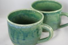 Share your favorite hot beverage with a friend! This listing is for a set of two (10oz) stoneware mugs. Each mug is dipped in matte green glaze,