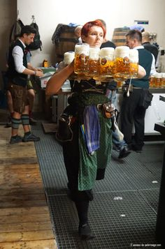 A waitress carrying more than 10 beer mugs at oktoberfest - each weighing almost 1 kilogramm