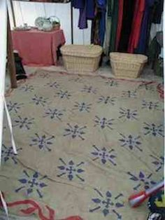 Burlap: My solution was to get wide lengths of burlap at the fabric store, sew them into large mats, and paint a design on them. Due to their loose-weave, they are easy to shake out, and don't get muddy. I use them straight on the ground. I like the burlap because it is light, stays clean and doesn't take up much room.