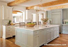 White cabinets with mint island; raw ceiling beams, similar to floor stain — Providence Design