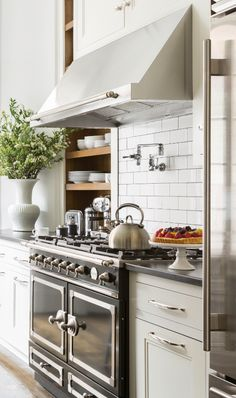 Beautiful modern black, white and wood kitchen with a French La Cornue oven, polished nickel cabinet hardware, and white subway tile backsplash.