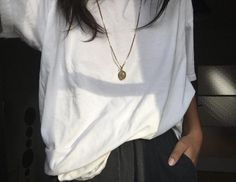 white t-shirt, gold locket necklace, and loose black pants