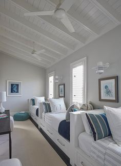 Beach house features a boys' bedroom filled with row of white built-in beds fitted with storage drawers dressed in white and blue striped bedding and pillows lining a single gray wall illuminated by white nautical wall sconces.