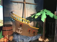 Shipwrecked VBS 2018 stage decorations - my palm tree from a carpet tube, umbrella and corobuff paper, ship made of foam board and a diy barrel from a cardboard box.