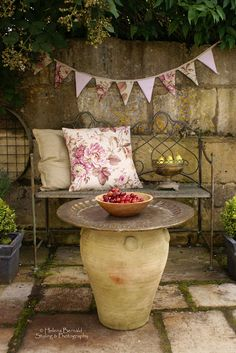 Garden bench with cushions, bunting, and table. I love how that table was made: Huge Tray over a large planter. Lovely.