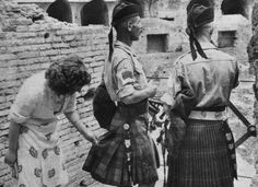 A curious Italian woman inspects the kilt of a Scottish soldier near the Coliseum after the liberation of Rome (1944)