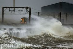A train passes through the coast at Saltcoats in Scotland, as Britain is braced for the worst as a combination of high tides, heavy rains and strong winds are expected to bring yet more severe flooding to parts of the country.