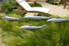 tall grass with fish sculptures swimming through