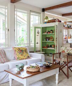 Sala de estar tem armário que expõem objetos de afeto da família e também serve como divisória entre ambientes.
