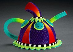 Rebecca Zimmerman Has done many wonderful teapots and one can tell when you are holding one of hers because of her unique colors and shapes.