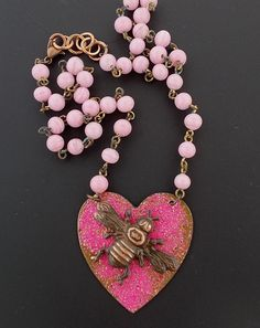 This necklace features a plated brass bee set on a brass heart that has been colorized using a cold enamel process. Vibrant pink color on the heart.  I